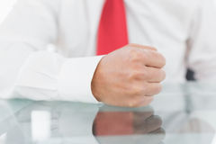 Mid section of a businessman with clenched fist on desk Royalty Free Stock Images