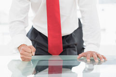 Mid section of a businessman with clenched fist on desk Stock Photo
