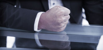 Mid section of businessman with clenched fist on office desk Royalty Free Stock Images