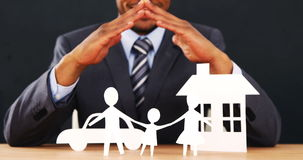 Mid section of businessman with cutout paper chain family with the protection of hands. On table in office 4k stock video footage