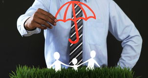 Mid section of businessman with cutout paper chain family with the protection of umbrella. On grass in office 4k stock footage