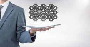 Mid section of businessman holding digital tablet with social media icon set Stock Photo