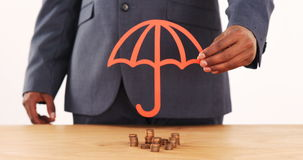 Mid section of businessman holding paper cutout of umbrella on stacks of coins. On table in office 4k stock video