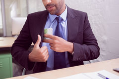 Mid section of businessman keeping currency in pocket Stock Image