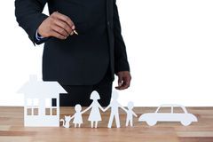 Mid section of businessman with paper cut out family, house and car at desk Royalty Free Stock Image
