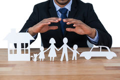 Mid section of businessman protecting paper cut out family, house and car with hands Stock Images