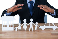 Mid section of businessman protecting paper cut out family, house and car with hands Stock Image