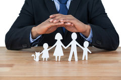 Mid section of businessman protecting paper cut out family, house and car with hands Royalty Free Stock Photo