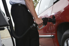 Mid Section Of A Businessman Refueling His Car Royalty Free Stock Images