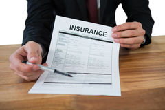 Mid section of businessman sitting at desk holding insurance contract Stock Image