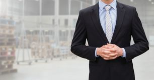 Mid section of businessman standing with hands clasped. In warehouse Stock Images