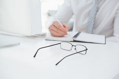 Mid section of a businessman taking notes Stock Photo