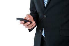 Mid section of businessman text messaging on mobile phone Royalty Free Stock Photos