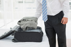 Mid section of a businessman unpacking luggage. At a hotel bedroom Stock Photo