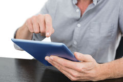 Mid section of a businessman using digital tablet at table Stock Image