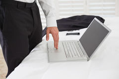 Mid section of businessman using laptop at hotel room Royalty Free Stock Photo