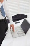 Mid section of a businessman using laptop at hotel room. Side view mid section of a businessman using laptop at a hotel room Royalty Free Stock Photography