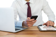 Mid-section of businessman using mobile phone and digital tablet with laptop on table. In office Stock Photos