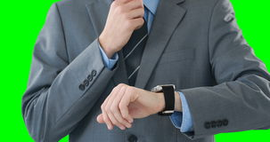 Mid-section of businessman using smartwatch. Against green background stock footage