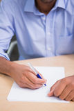 Mid section of businessman writing document at desk. Close up mid section of businessman writing document at office desk Royalty Free Stock Images