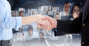 Mid-section of businesspeople shaking hands against interface background Stock Images