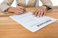 Mid section of businesswoman filling mortgage contract form. Against white background Stock Images