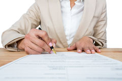 Mid section of businesswoman filling mortgage contract form. Against white background Stock Photography