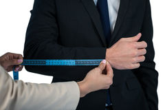 Mid section of businesswoman measuring businessman sleeve. Against white background Stock Photos
