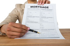 Mid section of businesswoman showing mortgage contract. Against white background Stock Images
