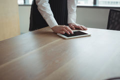Mid section of businesswoman using digital tablet on desk Royalty Free Stock Photos