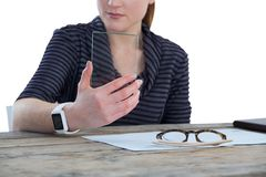 Mid section of businesswoman using glass interface. At table against white background Stock Photography