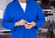 Mid section of car mechanic using mobile phone Royalty Free Stock Images