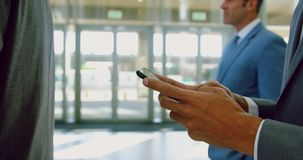 Businessman using mobile phone in a modern office 4k. Mid-section of caucasian businessman using mobile phone in a modern office. He is standing in a queue 4k stock video footage