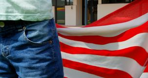 Mid section of Caucasian schoolboy holding American flag in school 4k stock video footage