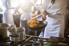 Mid section of chef cooking in kitchen stove Royalty Free Stock Photography