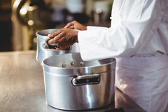 Mid section of chef holding cooking pot Stock Photos