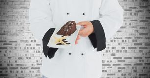 Mid section of chef holding pastry in plate Stock Photos