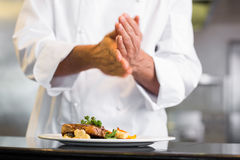 Mid section of a chef putting salt in kitchen Royalty Free Stock Photo