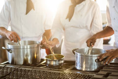 Mid section of chefs stirring in cooking pot. In a commercial kitchen Stock Photography