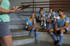 Mid section of coach standing by volleyball players Royalty Free Stock Photography