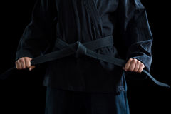 Mid section of confident karate player holding his belt Royalty Free Stock Photography