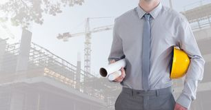 Mid section of construction man holding plan and hard hat Stock Photography