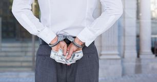 Mid section of corrupt businessman in handcuffs holding money Royalty Free Stock Photos