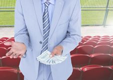 Mid section of corrupt businessman holding money in stadium Royalty Free Stock Photo