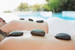 Mid section of a couple enjoying stone massage Royalty Free Stock Photos
