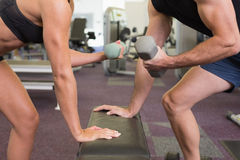 Mid section of couple exercising with dumbbells in gym Stock Image
