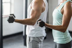 Mid section of couple exercising with dumbbells in gym Stock Photos