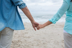 Mid section of couple holding hands on beach Stock Photography
