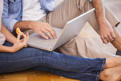 Mid section of couple sitting on floor using laptop Royalty Free Stock Photos
