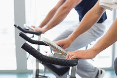 Mid section of couple working on exercise bikes at gym Stock Image